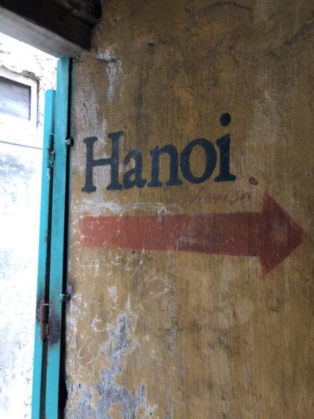 古い建物の壁にHanoiの文字と誘導する矢印マーク