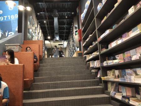 階段と隅に茶色いソファが置かれた書店内の様子