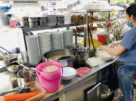 店先の調理場で女性が調理する様子