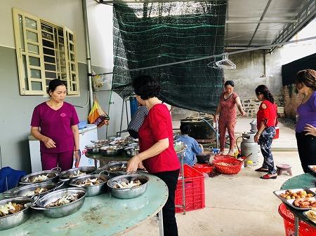 新婦の自宅庭で女性たちが料理をしている様子