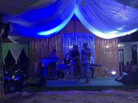 特設の会場で普段着の中年男女がカラオケで歌う