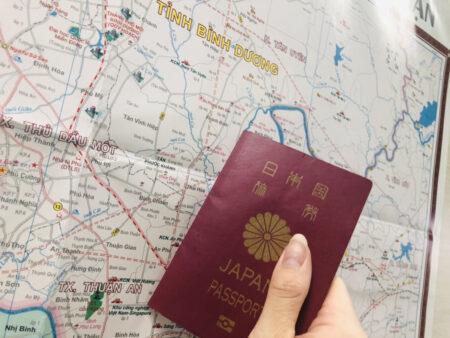 ベトナムの地図の前で日本国籍パスポートを持っている様子